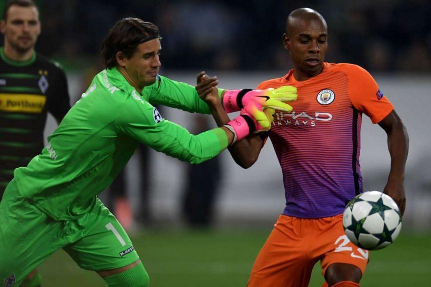 Moenchengladbach's Swiss goalkeeper Yann Sommer and Manchester City's Brazilian midfielder Fernandinho vie for the ball.