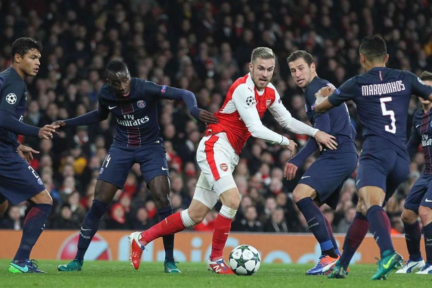 Arsenal's Aaron Ramsey (centre) is surrounded by Paris Saint-Germain players during the Uefa Champions League group A football match.