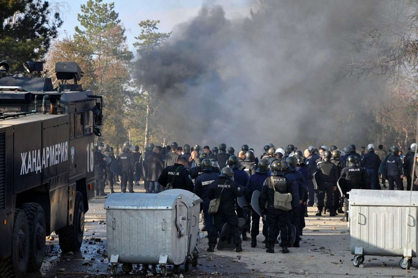 Bulgarian riot police stand near garbarge bins during clashes in the migrants reception centre in the town of Harmanli on Nov 24, 2016.