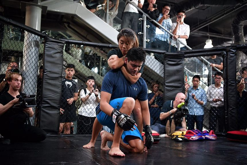 Olympic champion Joseph Schooling being given an MMA crash course by One Championship atomweight champion Angela Lee.