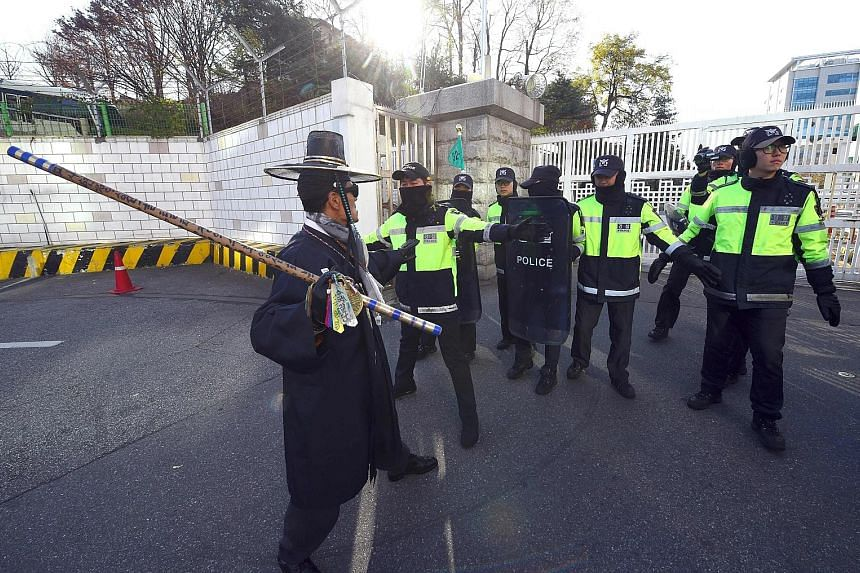 Policemen blocking a South Korean protester in the compound of the defence ministry during a rally against the signing of a controversial information-sharing agreement between South Korea and Japan yesterday.