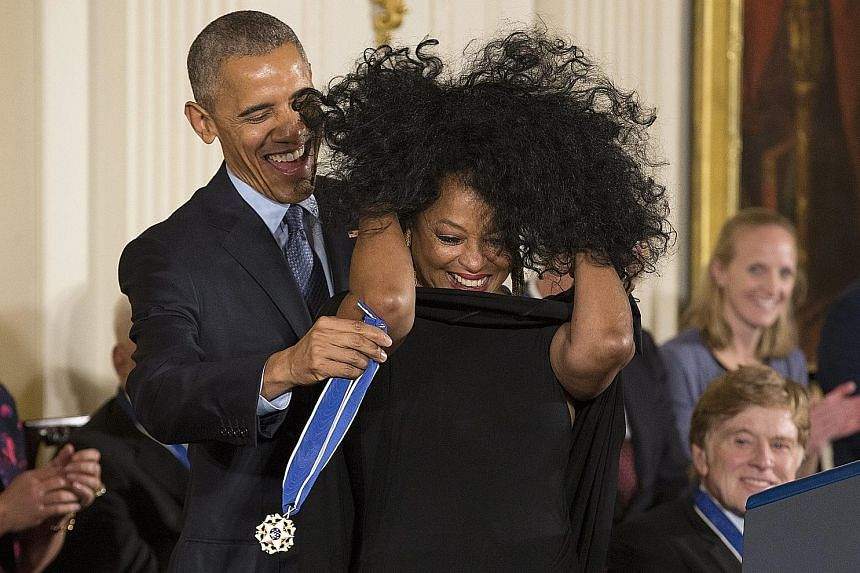 Unintentional funny moments included President Barack Obama putting the medal on towering basketball legend Kareem Abdul-Jabbar (above) and on singer Diana Ross (right), who had to adjust her enormous hair.