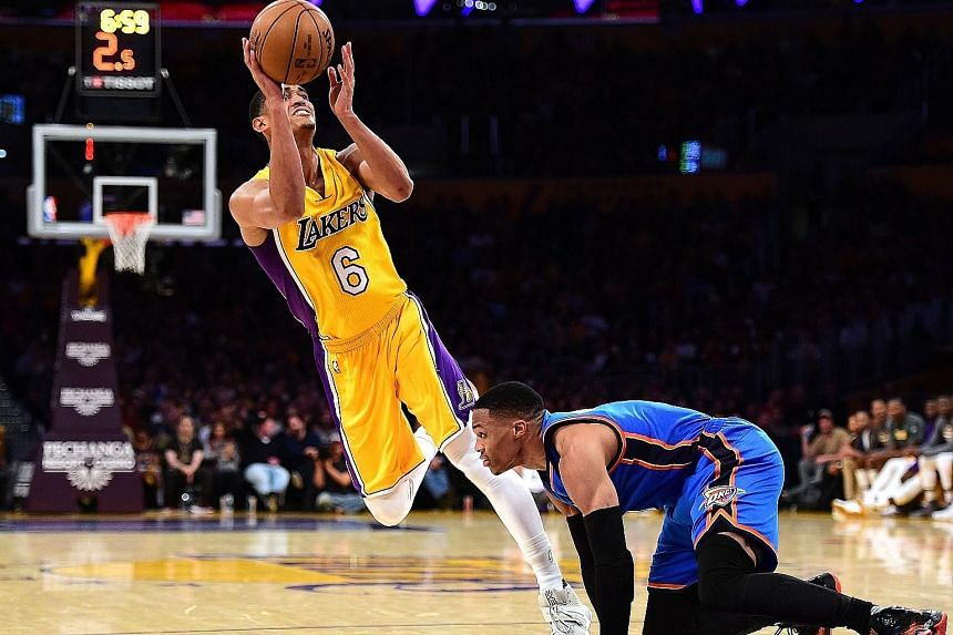 Jordan Clarkson of the Los Angeles Lakers scoring on his off-balance shot as he is fouled by the Oklahoma City Thunder's Russell Westbrook during a National Basketball Association game. The Lakers won 111-109 in the dying seconds to snap a nine-game