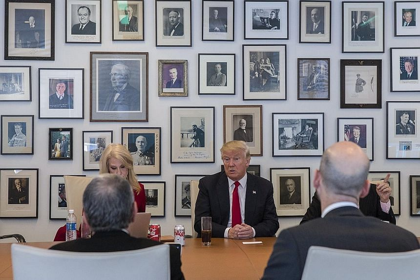 "Mr Trump with top adviser Kellyanne Conway during the interview with The New York Times at the Times building in New York on Tuesday. The President- elect eased off on his comments on climate change and dropped the ""lock her up"" pledge against Mrs Hi"