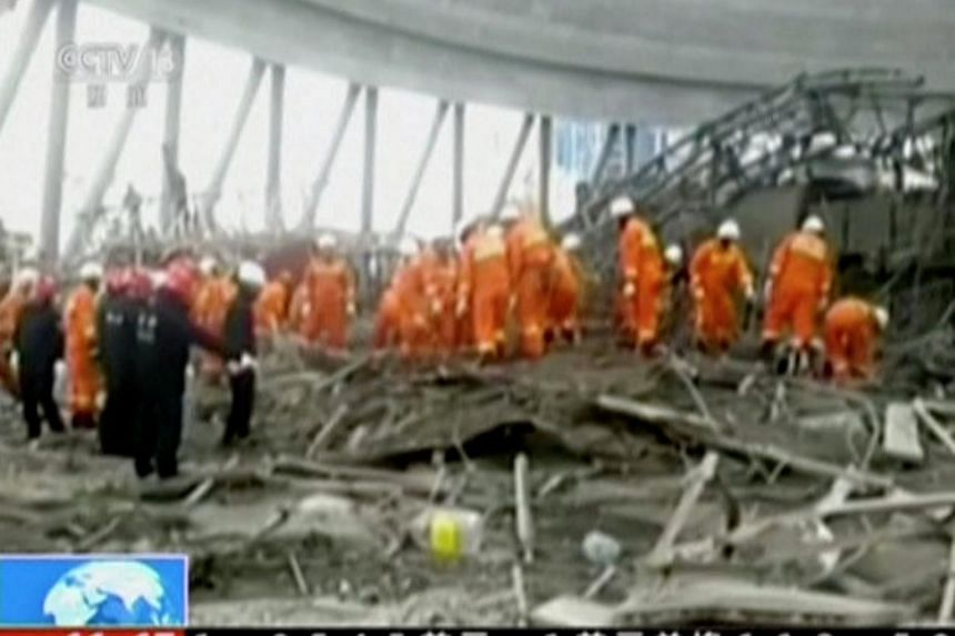 In this still image from a video, rescue workers are seen at the site of a platform under construction at a power plant's cooling tower in Fengcheng in eastern China's Jiangxi province, which collapsed on Thursday (Nov 24).