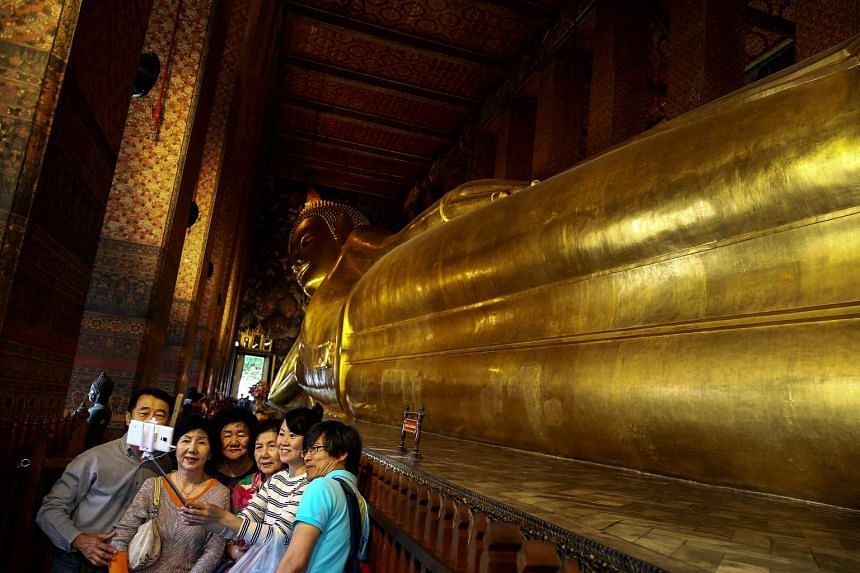 A group of Chinese tourists take a selfie next to the Reclining Buddha at Wat Pho in Bangkok, Thailand on Oct 3, 2016.