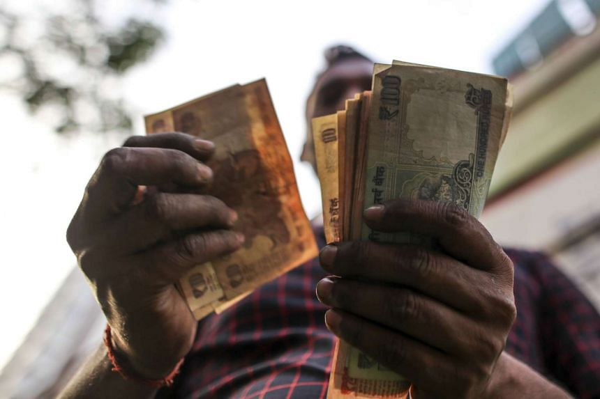 A vendor counts Indian rupee banknotes at a vegetable wholesale market in Mumbai on Nov 19, 2016.