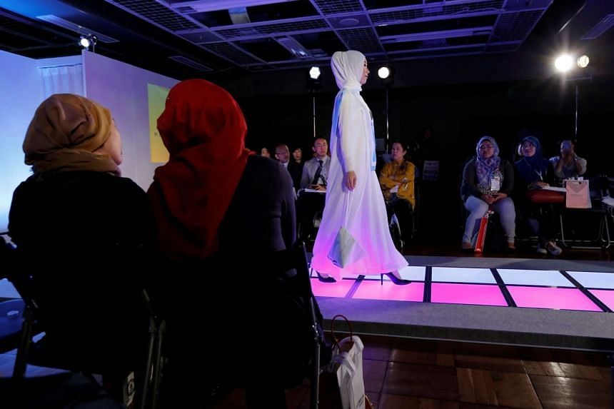 Muslim women look at a model presenting a creation by brand Meem Clothings during the Tokyo Modest Fashion Show at Halal Expo Japan in Tokyo on Nov 22, 2016.