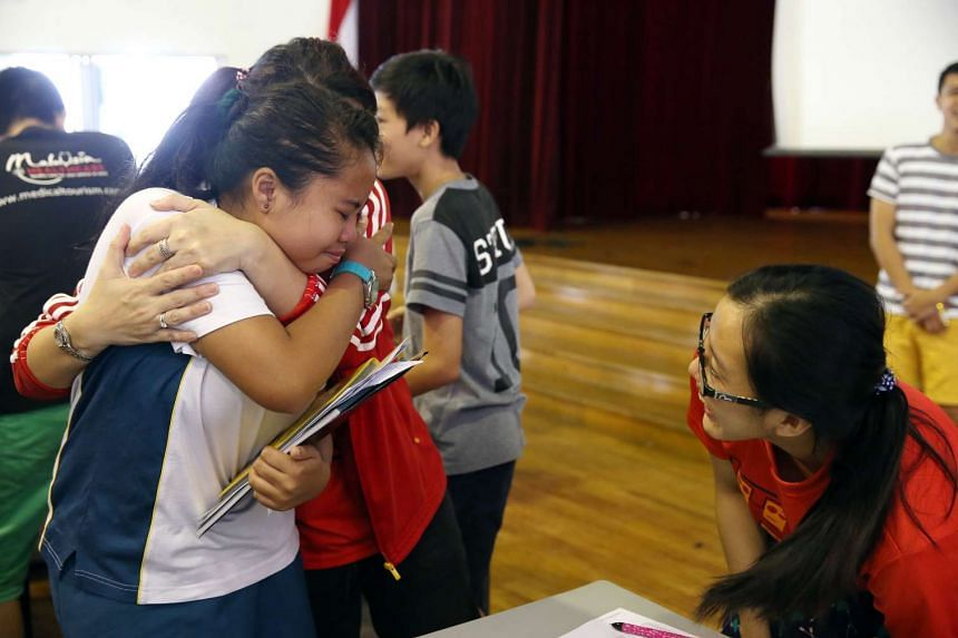 Putri Lydia Hemamalini, 12, congratulated by her teachers Mdm Samantha Lee and Mdm Po Mun Ying (right), after she received her PSLE results at Lianhua Primary School on Thursday (Nov 24).