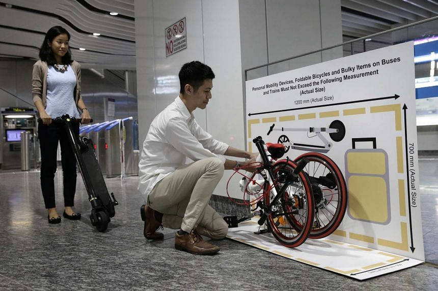 Land Transport Authority staff showing examples of a foldable bike and personal mobility devices such as a kick scooter that conform to the acceptable dimensions outside Little India MRT Station Downtown Line entrance on Nov 24, 2016.