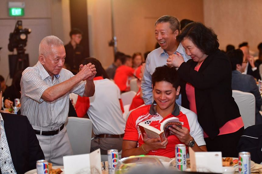 Swimmer Joseph Schooling peruses a book on Singapore's Olympians, while Singapore's first Olympic medallist Tan Howe Liang (left) is greeted by May Schooling (right).