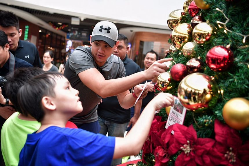 Joseph Schooling decorates a Christmas tree with kids from the Make-A-Wish Foundation at Kallang Wave Mall on Thursday (Nov 24).