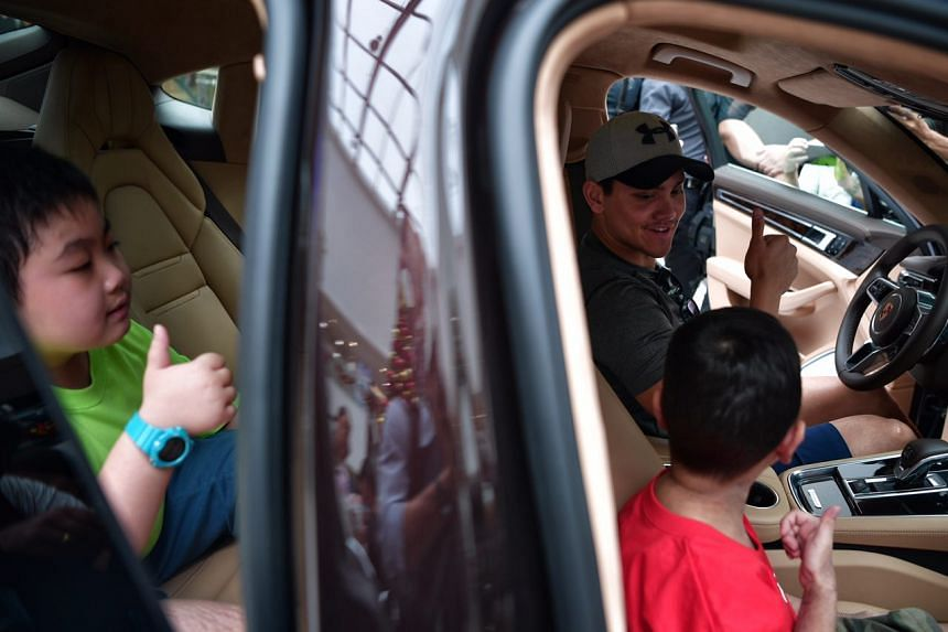 Joseph Schooling sits in a Porsche with nine-year-old kids Joshua Koh (left), Boon Kye Feng (right) and Joshua Ong (not pictured) from the Make-A-Wish Foundation at Kallang Wave Mall on Thursday (Nov 24).