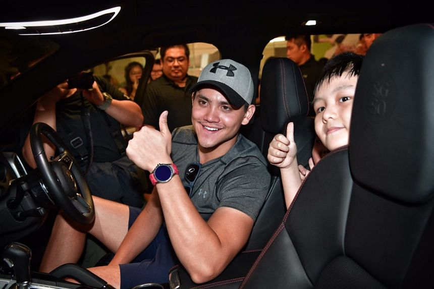 Joseph Schooling sits in a Porsche with nine-year-old kids Joshua Ong (right), Boon Kye Feng (not pictured) and Joshua Ong (not pictured) from the Make-A-Wish Foundation at Kallang Wave Mall on Thursday (Nov 24).