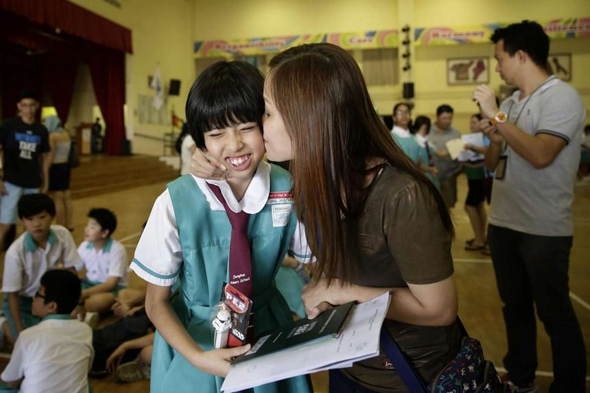 Primary 6 pupil Ong Jing Mei of Zhonghua Primary School receiving a kiss from her mother after getting her PSLE results, on Nov 24, 2016.