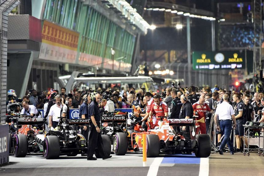 Mechanics stand near Formula driver race cars parked after the qualifying session of the Formula One Singapore Grand Prix.
