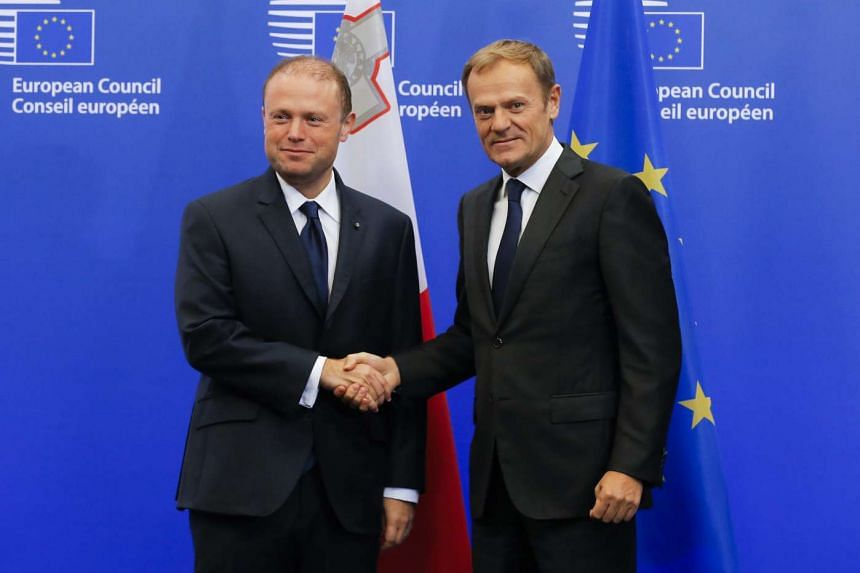 Malta's Prime Minister Joseph Muscat (left) is welcomed by European Council President Donald Tusk (right) prior to their meeting in Brussels on Nov 16, 2016.