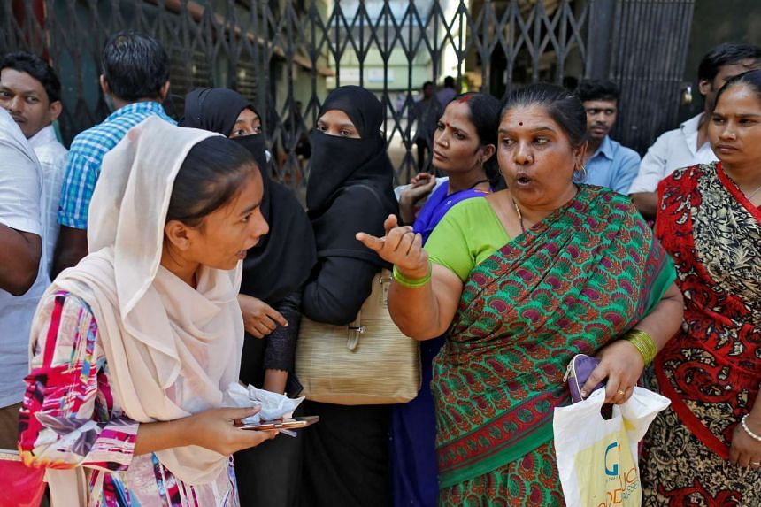 People argue with each other as they wait their turn to exchange or deposit their old high denomination banknotes outside a bank in Mumbai, India, Nov 24, 2016.