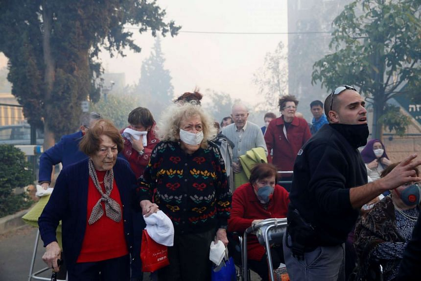 Emergency personnel evacuate elderly people as a wildfire rages in the northern city of Haifa, Israel, Nov 24, 2016.