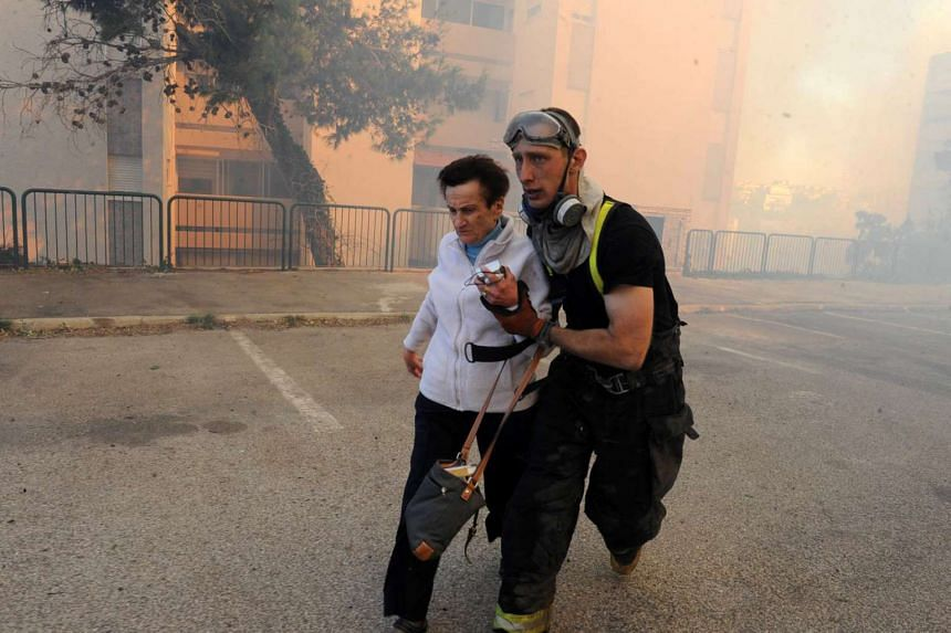 An emergency personnel member evacuates a woman as a wildfire burns in the northern Israeli city of Haifa, Israel, Nov 24, 2016