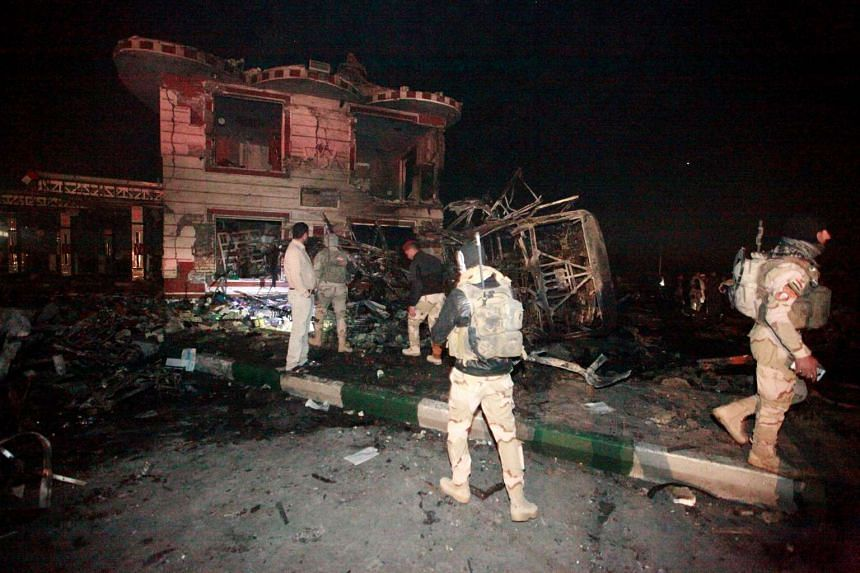 Iraqi security forces gather at the site of a suicide truck bomb attack, at a petrol station in the city of Hilla south of Baghdad, Iraq, Nov 24, 2016.