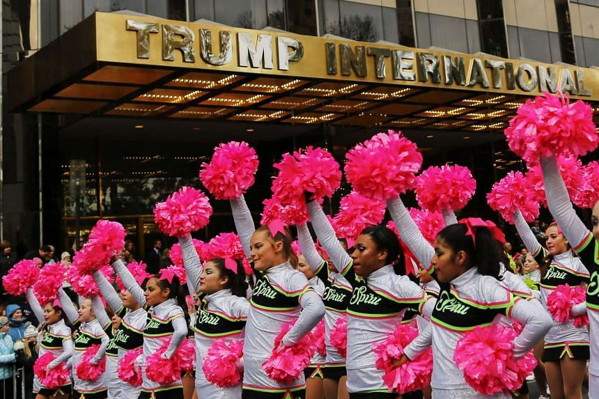Revellers pass by Trump International Hotel as they take part during the 90th Macy's Annual Thanksgiving Day Parade on Nov 24, 2016 in New York City.