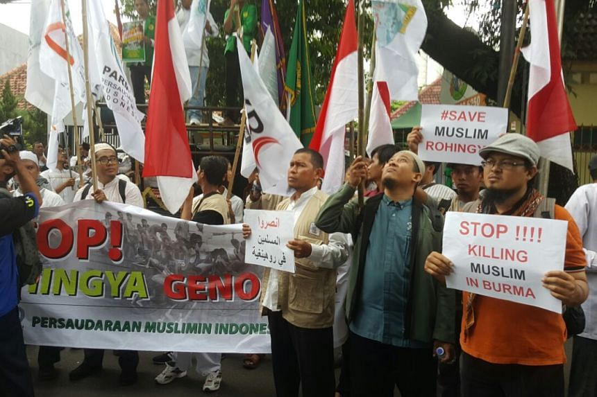 People holding placards and banners gather outside the Myanmar embassy in Jakarta to protest against the oppression of Rohingya Muslims.
