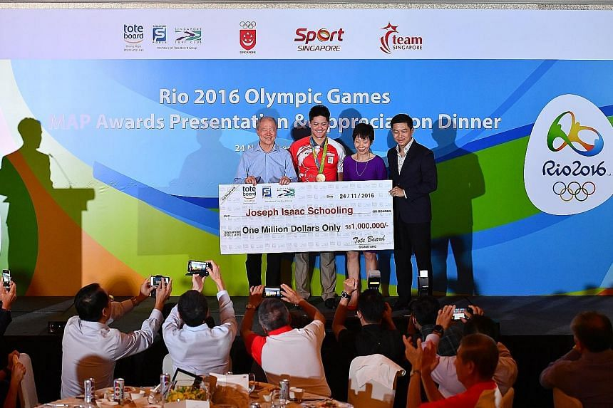 Joseph Schooling (in red) receiving a mock cheque for $1 million last night from Tote Board chairman Moses Lee (left), Minister for Culture, Community and Youth Grace Fu and Minister for Social and Family Development Tan Chuan-Jin, who is also presid