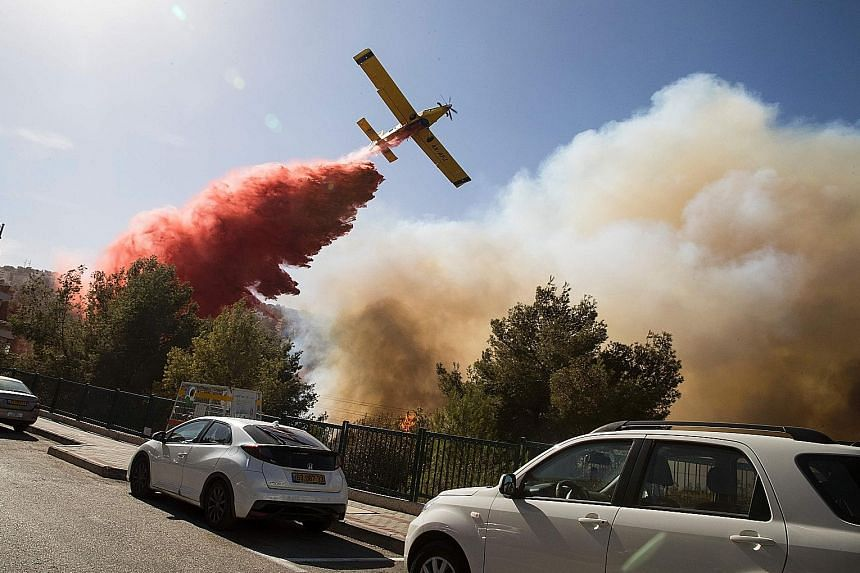 A firefighting plane helping to extinguish a bushfire in the northern Israeli port city of Haifa yesterday. About 50,000 Israelis fled their homes on the outskirts of the country's third city while others were trapped inside as firefighters struggled