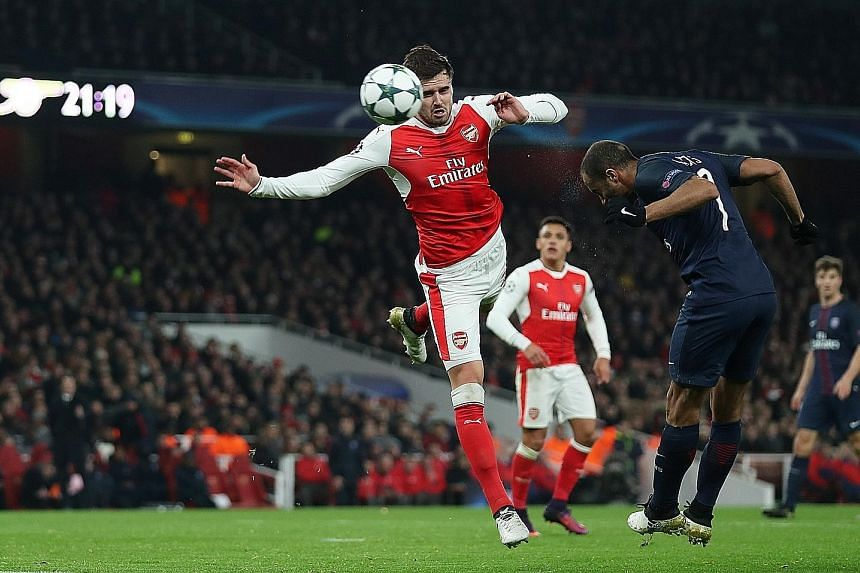 PSG's Brazilian midfielder Lucas Moura (right) heading the ball, which was deflected into the Arsenal net by Alex Iwobi (not pictured) for their equaliser in the 2-2 draw at the Emirates Stadium on Wednesday. The French champions can ensure top place