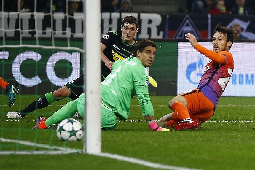 Manchester City's David Silva (right) scoring the equaliser in the 1-1 Group C match at Borussia Monchengladbach on Wednesday as goalkeeper Yann Sommer (centre) and Andreas Christensen look on. The drawn game was sufficient to put City into the Champ
