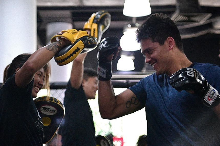 Joseph Schooling being given an MMA crash course by One Championship atomweight champion Angela Lee at Evolve MMA yesterday. While the swimmer would not enter the cage, he is open to incorporating some MMA moves into his training.