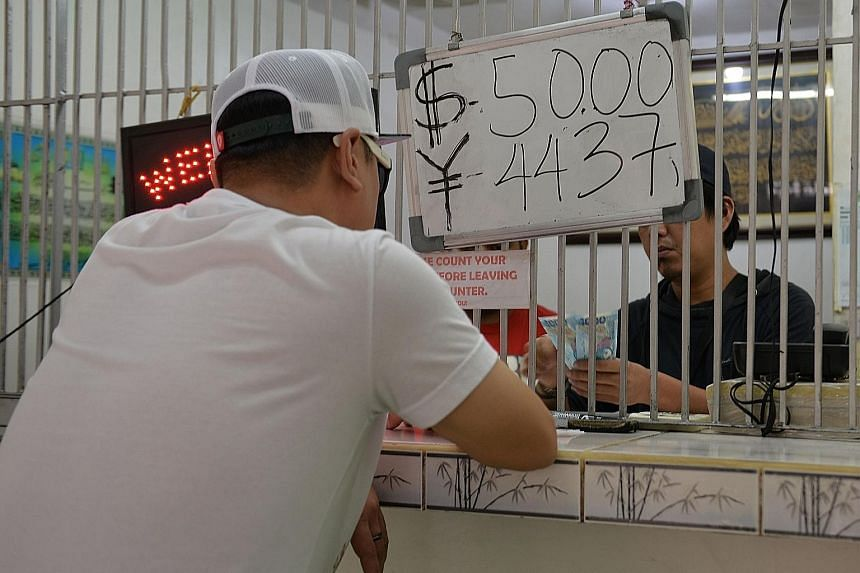 A moneychanger in Manila. The peso fell to its lowest level against the dollar in eight years yesterday.