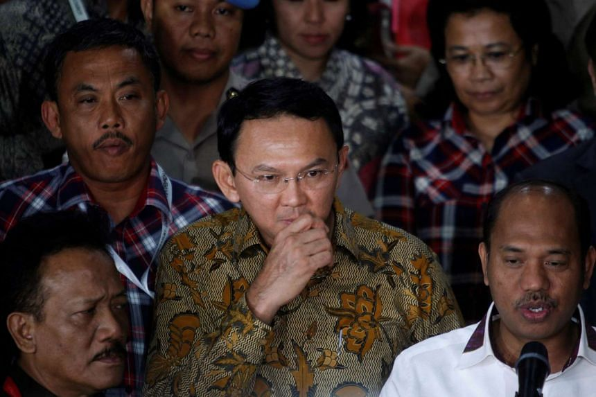 "Jakarta Governor Basuki Tjahaja Purnama (centre), known by his nickname ""Ahok"", is seen with supporters and members of his legal team outside police headquarters after questioning over blasphemy allegations in Jakarta, Indonesia, on Nov 22, 2016."
