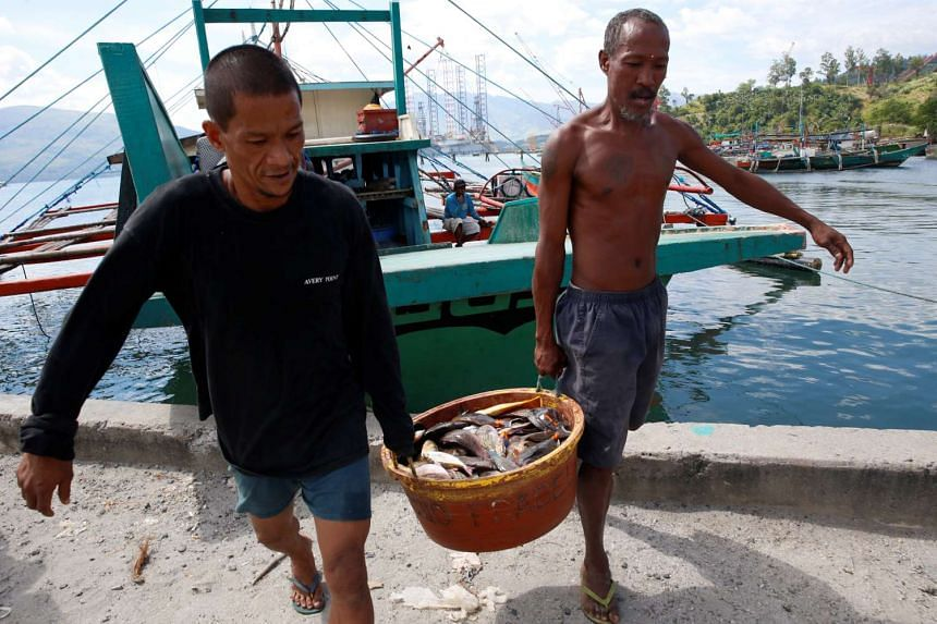 Fishermen, who has just returned from fishing in disputed Scarborough shoal, unload fish from a boat in Subic, Zambales in the Philippines on Nov 1, 2016.