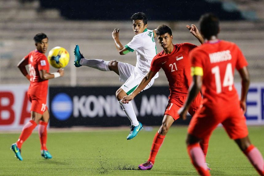 Benny Wahyudi (in white) of Indonesia in action against Safuwan Baharudin (#21) of Singapore during the AFF Suzuki Cup Group A football match between Singapore and Indonesia in Manila on Nov 25, 2016.