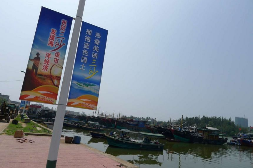 """Posters adorn lamp posts in Tanmen fishing village, urging locals to """"love Sansha city, embrace China's blue-water territory""""."""