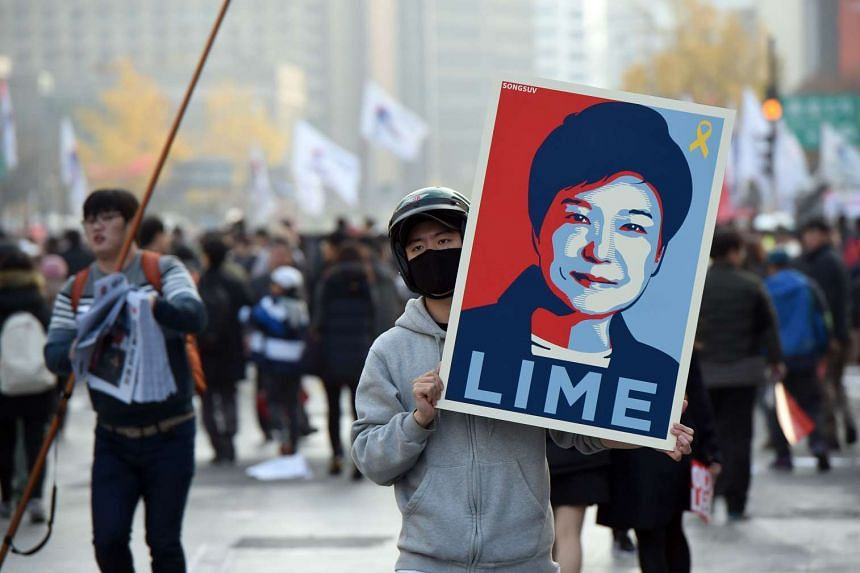 A protester holds a placard showing a portrait of South Korea's President Park Geun Hye during an anti-government rally in central Seoul on Nov 19, 2016.