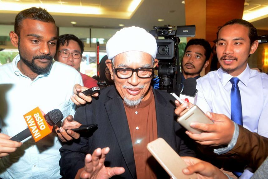 Parti Islam SeMalaysia president Abdul Hadi Awang (centre) surrounded by members of the media at the parliament house as he leaves the Dewan Rakyat, on Nov 23, 2016.