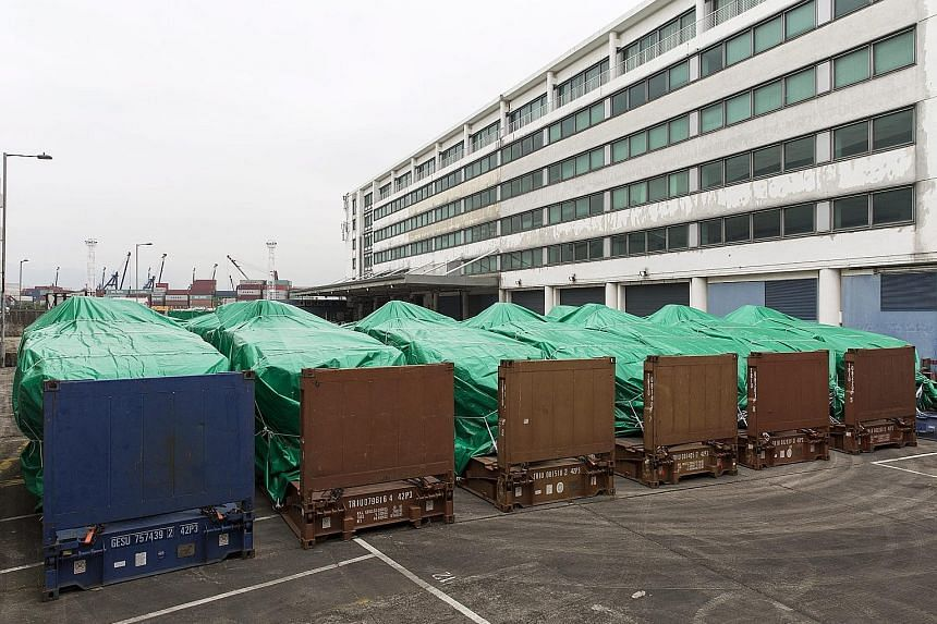 The armoured vehicles covered with green tarpaulins in a Hong Kong Customs and Excise Department facility in Tuen Mun yesterday. Nine Terrex Infantry Carrier Vehicles were seized by Hong Kong Customs at a port on Wednesday. They were being shipped fr