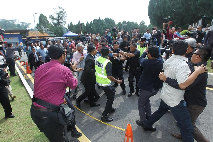 Mr Khalid (wearing a pink shirt and a red tie) being shielded by police and security personnel after he was attacked just outside the Parliament building on Thursday.