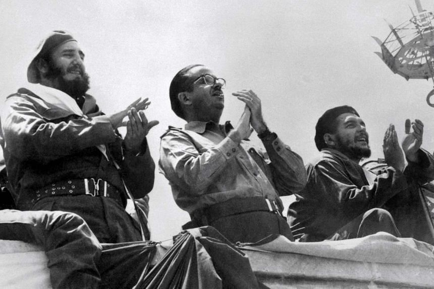 Former Prime Minister of Cuba Fidel Castro (left), wearing a beret, accompanied by Cuban President Osvaldo Dorticos (centre) and Ernesto Che Guevara, Minister of Industry applauding the May Day parade in the official Tribune in Havana, on May 1, 1961