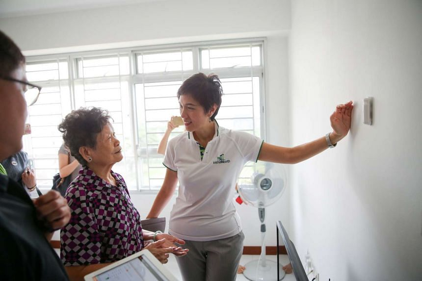 Mrs Josephine Teo talks to Madam Ng Siew Eng, who has sensors installed around her house.