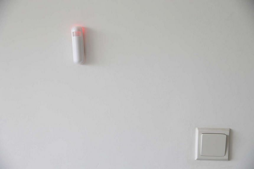 A wireless motion sensor (top left) installed on the wall of the living room.