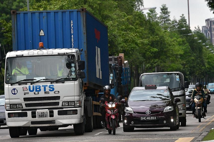 A motorcyclist riding closely to a heavy vehicle in Woodlands Avenue 12 yesterday. Being more exposed than other motorists makes motorbike riders the most vulnerable road users, with 4,875 motorcyclists and their pillion riders injured last year, a 5