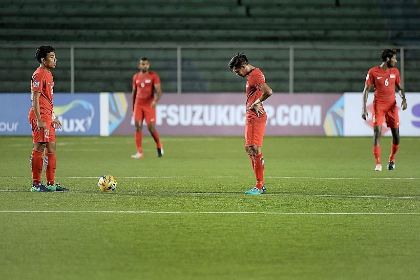 Singapore's Shahfiq Ghani (left) and Khairul Amri looking dejected after Indonesia scored their second goal in the final Suzuki Cup Group A match which ended 2-1.