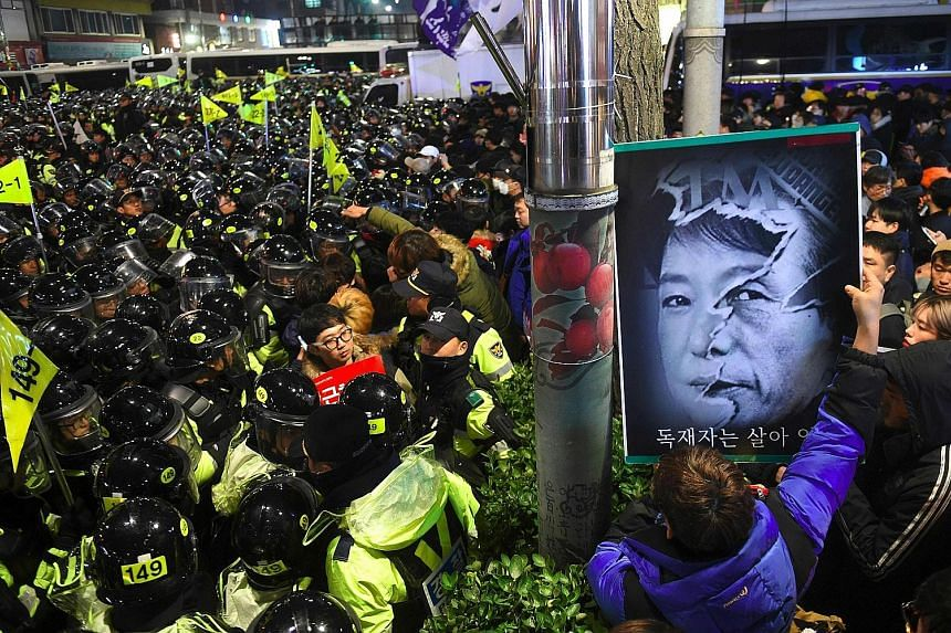 South Korean riot police grappling with protesters marching on the presidential Blue House in Seoul during a rally demanding the resignation of scandal-hit President Park Geun Hye yesterday. Lawmakers are considering a possible move to impeach Ms Par