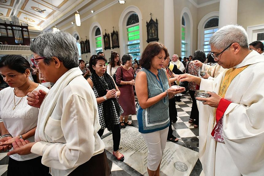 Catholics receiving communion from Archbishop Goh during mass at the newly restored Cathedral of the Good Shepherd last Sunday.