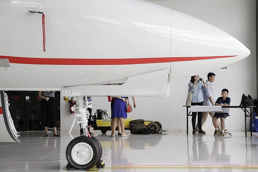 Nine-year-old Huo Xi Cheng sketching a picture of the Hawker 700 business jet which he got to see up close at Temasek Polytechnic's Aviation Academy on Friday.