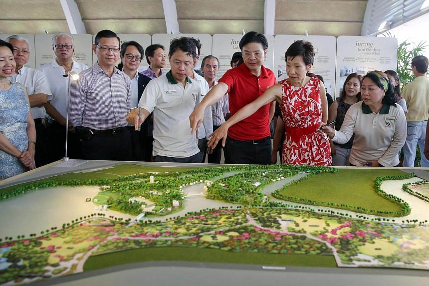 National Development Minister Lawrence Wong (in red) and Minister for Culture, Community and Youth Grace Fu look at a model of the Jurong Lake Gardens masterplan.